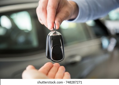close up photo of male hand giving car keys to female hand, indoors in car dealership
