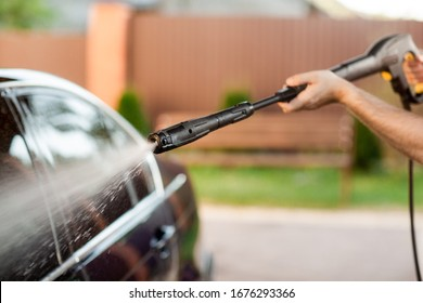 Close up photo of a man hands washes his car with a large head of water from a karcher on open air. Cleaning and disinfection. Security measures during the epidemic