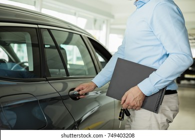 Close up photo of man opening a car door, holding a car door handle with one hand and folder and car keys in  another hand, getting into a car concept