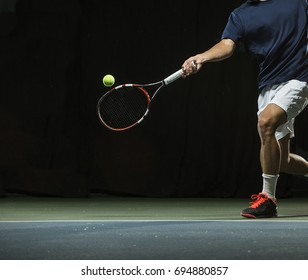 Close up photo of a man swinging a tennis racquet during a tennis match.