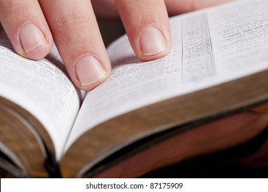Close photo of man thumbing through the Bible. Macro.