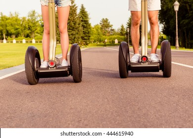 Close up photo of man and woman riding electric gyropode