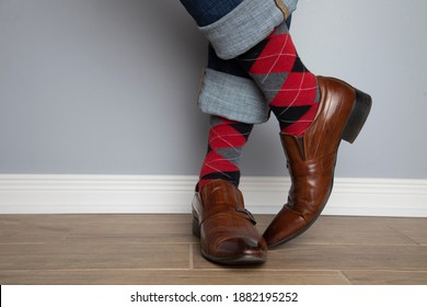 Close up photo of a man's feet wearing leather shoes, jeans and colourful socks. The photo is taken indoors against a wall.