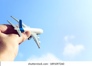 close up photo of man's hand holding toy airplane against blue sky with clouds. filtered image