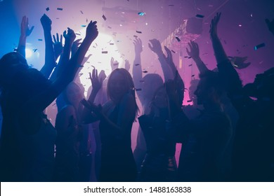 Close up photo of many party people dancing purple lights confetti flying everywhere nightclub event hands raised up wear shiny clothes