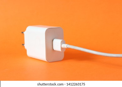 Close up photo of mobile phone USB charger isolated on orange background. Smartphone battery charger, micro USB or type C. Editorial image.