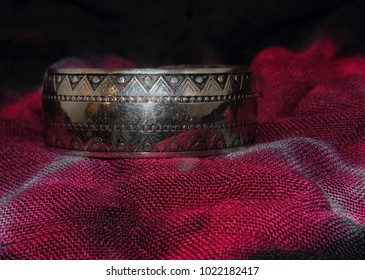 Close up photo of a Moroccan berber silver plate bracelet on a purple dyed fabric.