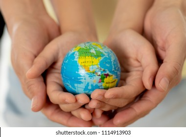 close up photo of mother and child holding hands with a world globe in their hands in better world idea protection and education concept