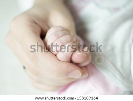 Close up photo of mother holding infant hand