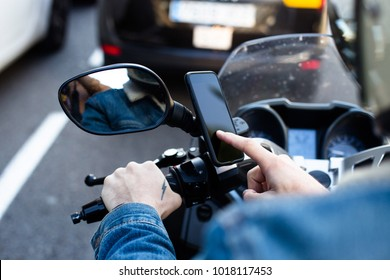 Close up photo of motorcycle or maxi scooter driver in helmet use smartphone application to find geo location. Uses phone mobile technology in every day life. big city traffic jam and future app