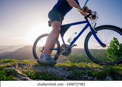 Close up photo from a mountain biker riding his bike ( bicycle) on rough rocky terrain on top of a mountain, wearing no safety equipment. Adrenalin junkie.