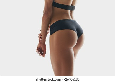 Close up photo of muscular woman legs isolated on white background. Woman bodybuilder buttocks