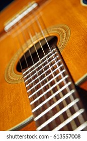 A close up photo of the neck and body of a 1970's six string classical guitar (also known as a Spanish guitar), with nylon strings.  Shallow depth of field.