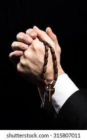 Close up photo of old man hands praying to God with rosary on black background