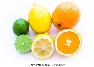 Close up photo of one cut-in-half slice of lime, lemon, an orange, with one  whole lime, lemon, an orange behind. The background is isolated.