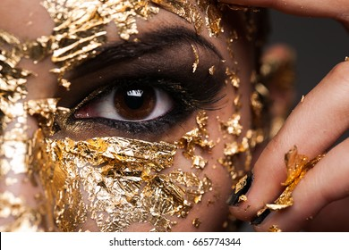 A close photo of a person in a gold mask with smoky eyes
