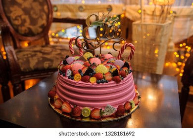 close up photo of a pink bithday cake decorated with fruits, candies and macarons for a little girl