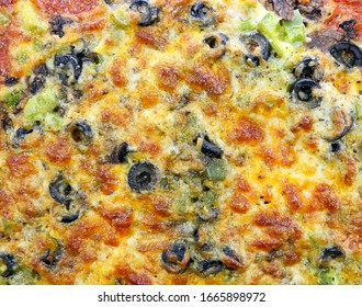 Close up photo of a pizza, topped with baked cheese, olives, green peppers, sauce, and pepperoni.