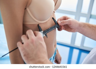 Close up photo of plastic surgeon using calipers to anthropometry female patient body