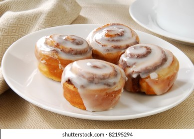 A close up photo of a plate of cinnamon rolls