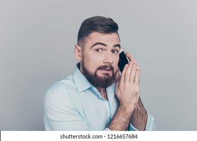 Close up photo portrait of busy noisy talking on telephone guy holding cellular in hand looking at camera isolated gray background
