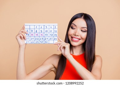 Close up photo portrait of pretty cheerful cute dreamy brunette brown haired lady holding showing handmade calendar in hand with three crossed days isolated on pastel beige background