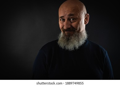 close up photo, portrait of a serious, thoughtful, bearded man on a dark background confident and dramatic looking straight. Concept of male portrait.  Low key
