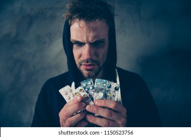 Close up photo portrait of unhappy tired exhausted with black eyes bearded hipster wearing sweater with hood showing many pills in hand isolated gray background
