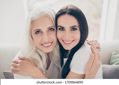 Close up photo of positive cheerful affectionate two people aged mom and her daughter sit couch sofa enjoy hug each other wear white t-shirt in living room