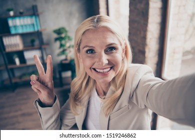 Close up photo of positive cheerful blonde hair middle aged businesswoman leader make selfie greet her clients partners investors make v-sign in workforce company office