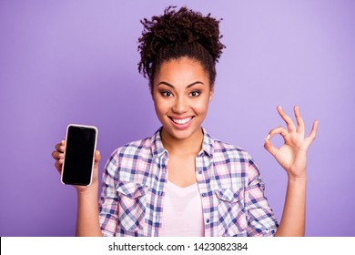 Close up photo positive cheerful lady student beautiful top-knot hold hand modern technology advise decision excellent choice recommend advertise trendy stylish plaid shirts isolated purple background