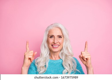 Close up photo of positive cheerful old woman point index finger up copyspace present adverts promotion recommend suggest select wear jumper isolated over pink color background