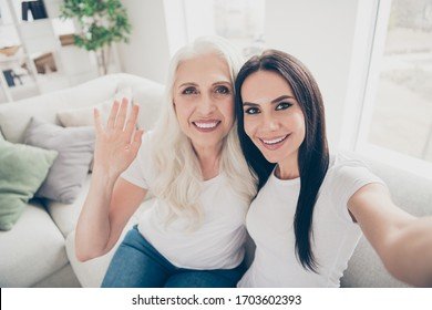 Close up photo of positive old woman mom her daughter make selfie have video call relatives abroad senior person sit comfort couch wave hand say hi hello in house indoors