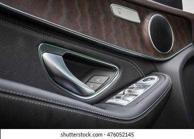 Close up photo of the premium-segment car door inner panel with open-pore ash wood trim. Hi-Fi speaker. Metal buttons of the window risers panel on the door armrest.