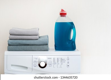 Close up photo of preparation to laundry process. White washing machine with bottle of blue gel soap standing isolated inside bright apartment interior ready to use