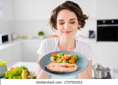 Close up photo of pretty housewife lady chef hold ready grilled salmon trout fillet steak with garnish cook dinner one person portion eyes closed wear apron t-shirt modern kitchen indoors