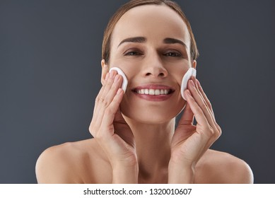 Close up photo of pretty lady with naked shoulders standing isolated on gray background. She removing maquillage using clean cotton pads