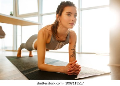 Close up photo of pretty lady in sporty top and leggings practicing fitness on yoga mat and listening music in earphones at home with big windows on background