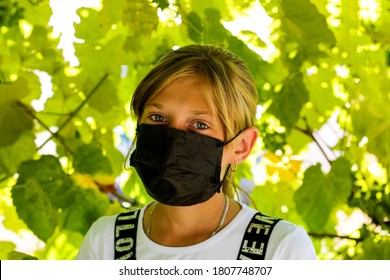 Close up photo of pretty positive cheerful child look have covid-19 quarantine her family friends wear black mask  Portrait of a girl going to school. Green nature background. Selective focus.