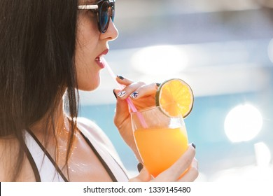 close up photo of pretty slim woman with long dark hair standing near the pool with a cocktail wearing white stylish swimwear and sunglasses. concept of luxury holiday time. free copyspace