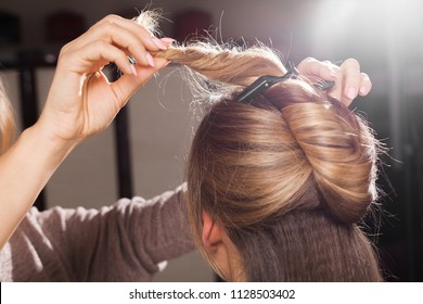 close up photo of professional hairdresser making an unusual coiffure to a brown haired young model in a beauty salon