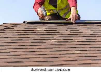 Close up photo of professional worker with electric drill installed tiles on top of the roof new modern house under construction