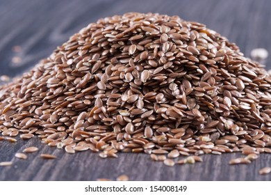 Close up photo of a raw eco food - dark brown linseeds placed on a dark wooden background.