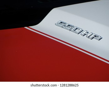 Close up photo of red and white car hood with horsepower visible