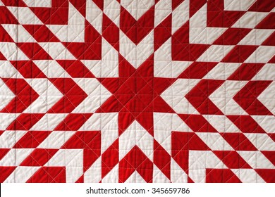 Close up photo of a red and white Lone Star quilt, a traditional American patchwork design, also known as Texas Star or Star of Bethlehem