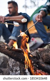 Close up photo of roasting marshmallows over the fire near tent in camping. Focus on fire. Young tourists having fun near the fire in the nature on the background