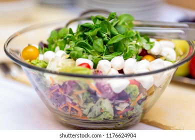 Close up photo of salad bowl with mozzarela balls, sliced carrot, green leaves, cantaloupe.