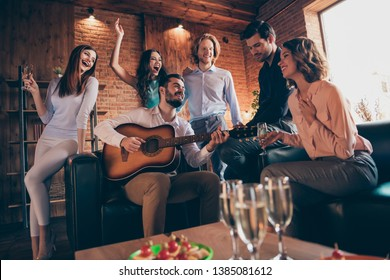 Close up photo serenade gathering best friends hang out vocal soloist play guitar fiance bride surprise romantic she her ladies he him his guys wear dress shirts formal wear sit sofa loft room indoors