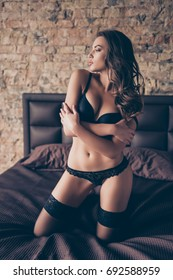 Close up photo of sexy naughty young brunette lady, in seductive nice silk underwear and stockings, on the brown sheets on bed, waiting for her lover, with crossed hands