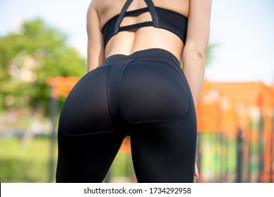 Close up photo of shapely woman's buttocks in black sport leggings at park